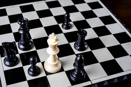 Chess king standing wins the game of chess setup on dark background. Chess concept save the king and save the strategy, game over.