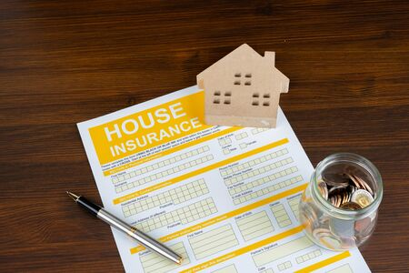 A conceptual image of a scale house and mortgage forms for the people buying a house. Dealing contract.