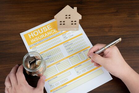 A conceptual image of a scale house and mortgage forms for the people buying a house. Hands that are signing a home purchase contract