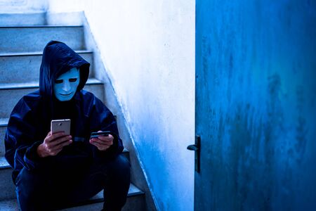 Hacker wearing a white mask and hoodie holding credit card and using smartphone. Cyber crime concept, Data thief, internet attack, darknet and cyber security concept.