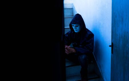 unrecognizable young man white mask and hoodie sitting on old stairs,. Sadness, despair, dark, concept