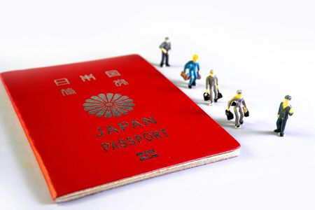 Small figure people and Japanese passport. Travel to the country.