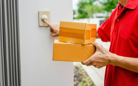 Young delivery man in red uniform standing at the door with parcel post box press ring bell in front of the house to delivery of the good, Deliver packages to recipients quickly, Home delivery concept.