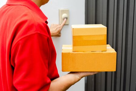 Delivery man in red uniform standing at the door with parcel post box press ring bell in front of the house to delivery of the good, Deliver packages to recipients quickly, Home delivery concept. 写真素材
