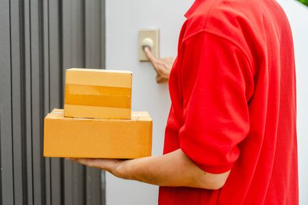 Young delivery man in red uniform standing at the door with parcel post box press ring bell in front of the house to delivery of the good, Deliver packages to recipients quickly, Home delivery concept