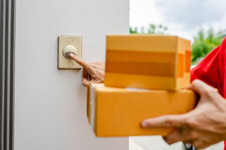 Delivery man in red uniform standing at the door with parcel post box press ring bell in front of the house to delivery of the good, Deliver packages to recipients quickly, Focus on the door jingle.