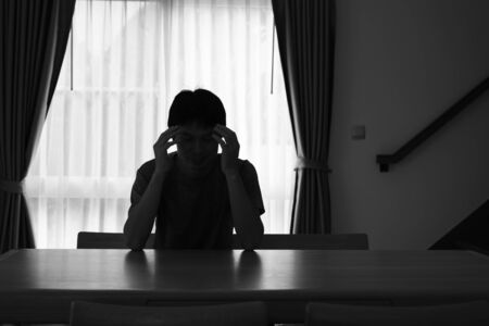 Sad man silhouette sitting on the table closed with curtains in home, Depression and anxiety disorder concept.