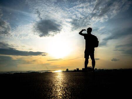 Mann, der auf der Draufsicht auf den malerischen Sonnenaufganghintergrund steht Übersehen Einer der Hotspots, um den Sonnenuntergang zu beobachten? Standard-Bild