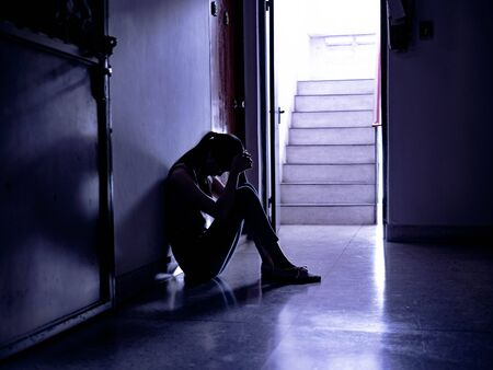 Silhouette of a sad young girl sitting in the dark leaning against the wall, thinking about problem with relationships or work, feeling despair and anxiety, loneliness, having psychological trouble.