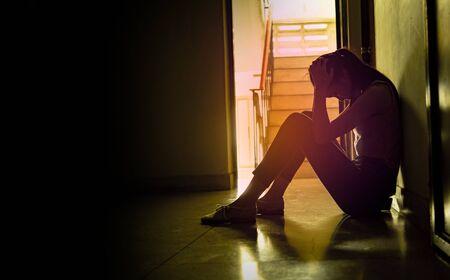 Sylwetka smutna młoda dziewczyna siedzi w ciemności, opierając się o ścianę, przemoc domowa, problemy rodzinne, stres, przemoc, pojęcie depresji i samobójstwa. skopiuj tło dla tekstu