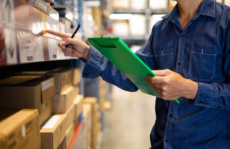 Manager man worker doing stocktaking of product management in cardboard box on shelves in warehouse. Physical inventory count. Male professional assistant checking stock in factory. Stockfoto