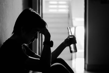 Silhouette of drunken man drinking beer are having stress in life and unable to find a solution and no advisor, from work problems And a failed family life.