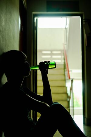 Silhouette of drunken man drinking beer are having stress in life and unable to find a solution and no advisor, from work problems And a failed family life. copy space background for text. Stock fotó