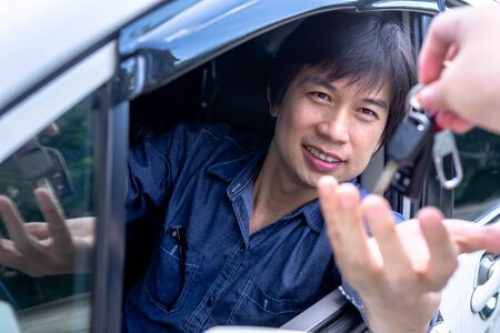 Asian man sitting in a can and is going to start the engine - the concept of buying a used car or a rental car. 스톡 콘텐츠