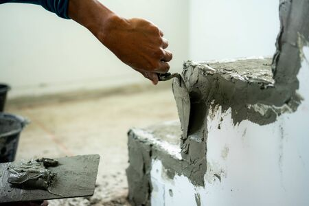 Construction worker with trowel plastering. Reklamní fotografie