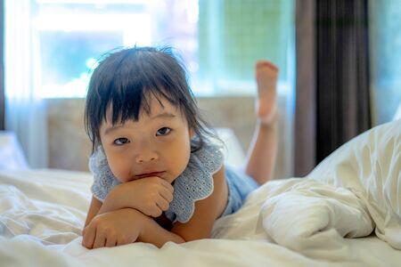cute smiling little asian girl woke up in white bed. Reklamní fotografie