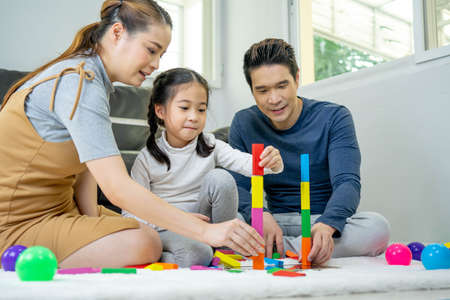 Asian parents playing with colorful blocks with daughter in the living room. Happy family concept. Standard-Bild