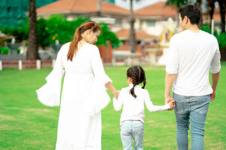 Asian family father and mother holding little girl on back and having fun moments good time in park. Standard-Bild