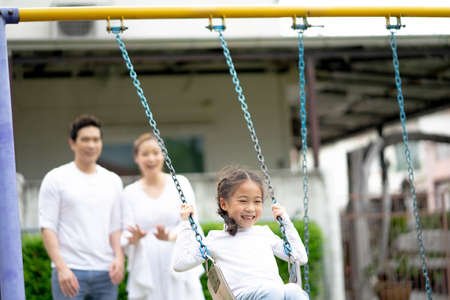 Happy Family time, Parents with daughter riding on a swing. Beautiful family is having fun outside.