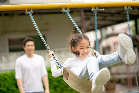 Young girl having fun on the swing. Her father swinging and they are both enjoying it. Happy family and childhood lifestyle. Standard-Bild