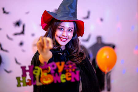 Girl holding up a Happy Halloween sign at a Halloween party.