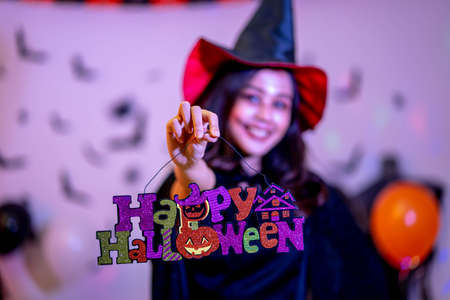 Girl holding up a Happy Halloween sign at a Halloween party