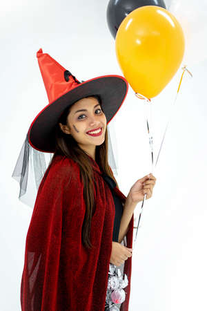 Beautiful young woman in witches hat and short dress holding black and orange air balloons.