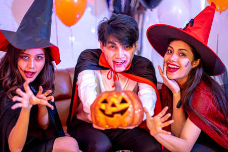 Group of Young Happy Friends Wearing Halloween Costumes having Fun at Party in Nightclub Standard-Bild