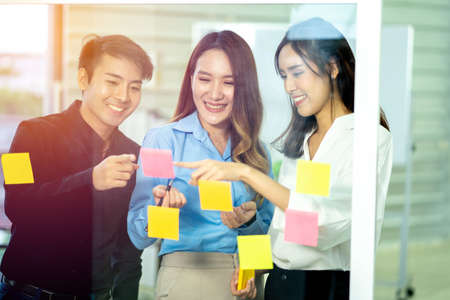 Group of young Asian business colleagues in team casual discussion, Start up partners are working in casual clothes, happy women having friendly conversation about business information having meeting in coworking office.