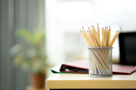 pencils stand on a wooden table in a ray of sunlightOffice with shallow dof on background of working space Stock Photo