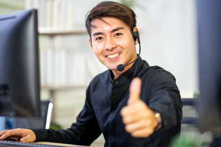 Cheerful male customer service operator showing thumbs up in office. Service Mind.
