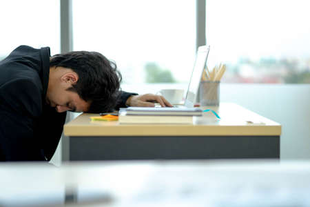 Exhausted sick tired male manager in office sad boring sitting with head down on laptop. Frustrated worker mental health problems. Standard-Bild