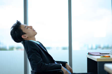 Businessman sitting at workplace near feeling Tired exhaustion and tiredness after long hard working day, overwork and stressful work.
