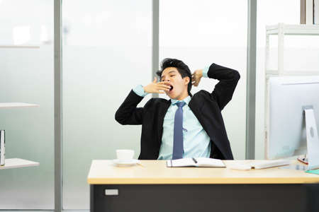 Bored Businessman sitting at workplace near computer feeling sleepiness exhaustion and tiredness after long hard working day. Concept of chronic fatigue, overwork and stressful work