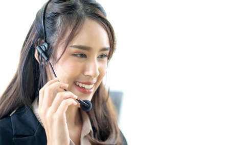 Smiling female customer support operator with headset working in office, Asian young woman working in call centre. Standard-Bild