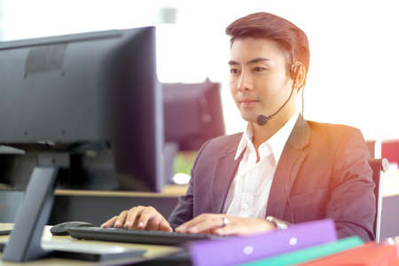 Young handsome male customer support phone operator with headset working in call center. Professional operator concept.