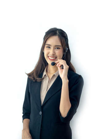 Photo of beautiful young asian call center operator standing near white background. Woman with headphones looking at camera and smiling Standard-Bild