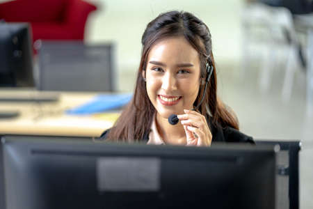 Portrait of happy smiling female customer support phone operator at workplace. Professional operator concept.
