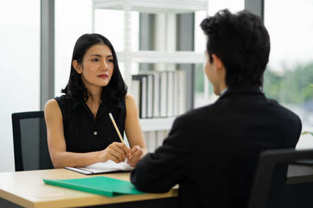 Beautiful manager woman talking to a male job applicant at the desk, interviewing, Rear view at a man. Business concept photo