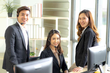 Asia Group of call center workers or Confident business team with headset. Technical support operators concept. Standard-Bild