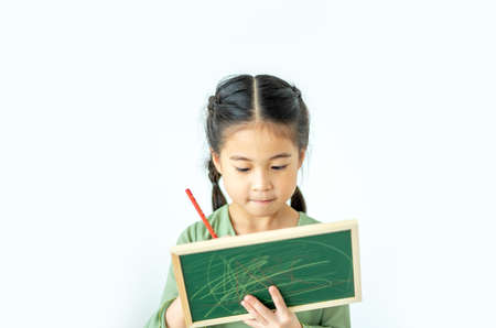Cute asian little girl holding a blank blackboard and Writing something.