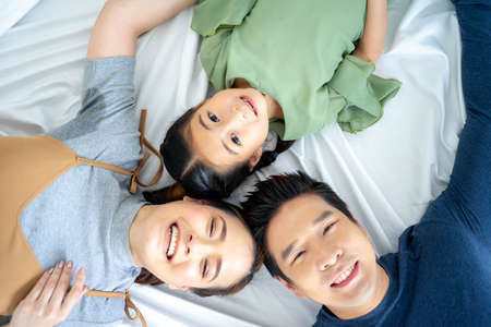 Asian family parents and daughter laughing lying on bed together, happy family with children bonding having fun enjoy funny moments in bedroom, top view from above. Standard-Bild