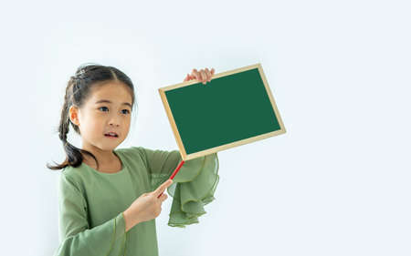 Cute asian little girl holding a blank blackboard with space for text.