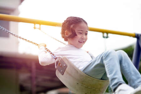Young girl having fun on the swing. Happy childhood lifestyle.