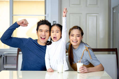 Asian family child girl and her father and mother drinking milk, having breakfast at kitchen. Happy family morning concept.