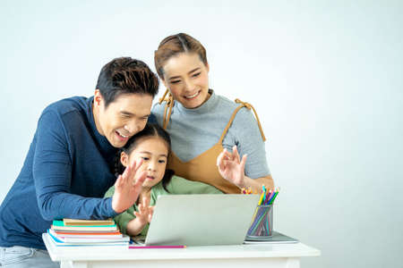 Father, mother and their daughter are smiling while spending time together with child are watching something on the tablet. studying and Education concept. Standard-Bild