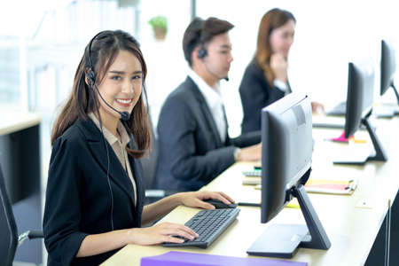 Call center worker accompanied by her team. Smiling customer support operator at work. Professional operator concept. Standard-Bild