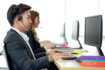 Side view of line of call centre employees are smiling and working on computers. Businesspeople In A Row Wearing Headset Working Together