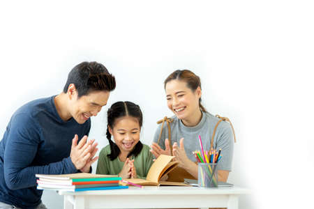 Asian young mother and father with little daughter sit at desk learning and making homework spending free time together at home. Education concept.