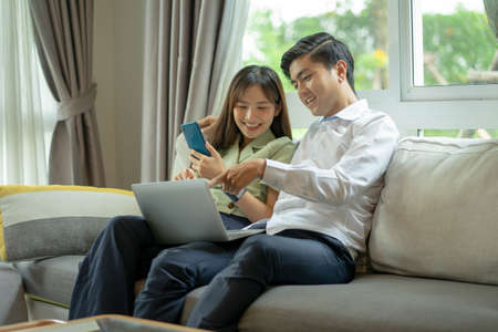 Asian couple smiling and looking at each other happily chatting. Are shopping online at home, using internet banking services. Standard-Bild